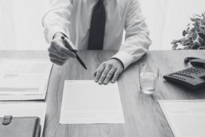 Eine Person gibt seinem Kunden einen Vertrag zum unterschreiben