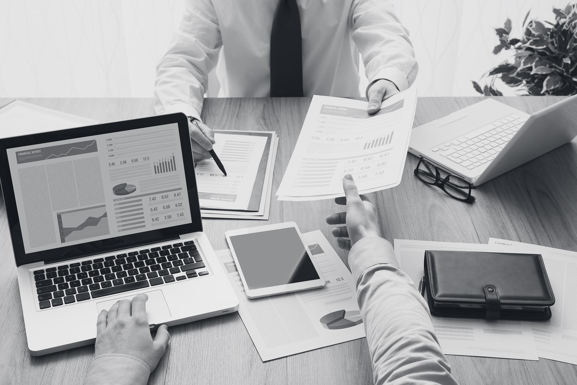 2 Personen arbeiten mit einem Laptop und analysieren Finanzen